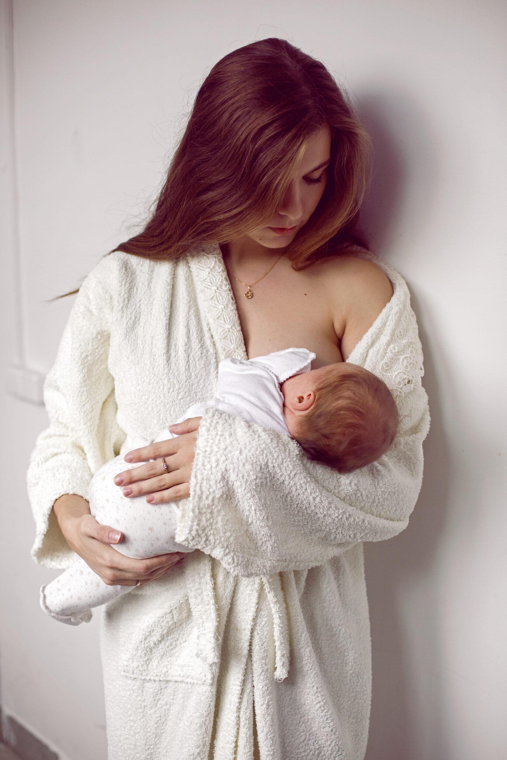Mother in cozy white robe breastfeeding infant