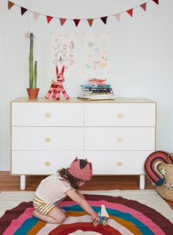 Child playing on Oeuf Rainbow Rug in front of Oeuf Fawn Dresser