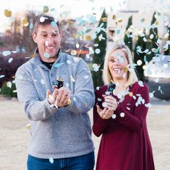 Couple using gender reveal poppers for boy